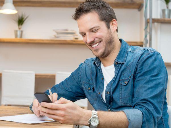 junger-mann-sucht-nach-jobs-per-hokify-app-und-lacht
