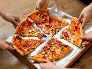 Mitarbeiter greifen nach Pizzastücken.
