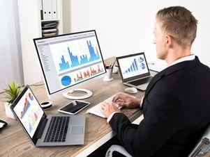 Mann sitzt vor zwei Laptops und einem Computer, auf denen die Konjunkturschwankungen abgebildet sind.