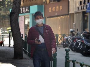 Ein-Mann-geht-in-Macau-China-mit-einer-Schutzmaske-auf-die-Straße-um-eine-Infektion-mit-dem-Coronavirus-zu-verhindern