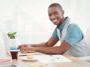 Junger Mann sitzt vor seinem Laptop und verfasst sein perfektes Anschreiben.