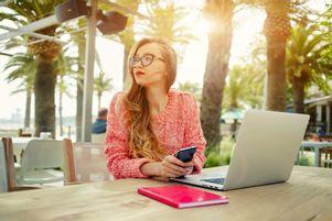 Junge Frau fühlt sich durch die Entspannungsübungen am Arbeitsplatz wie im Urlaub.
