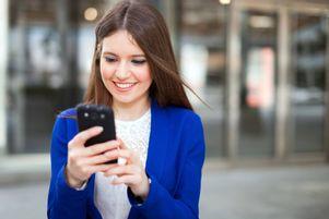 Junge Bewerberin kommuniziert über ihr Smartphone mit dem Unternehmen.