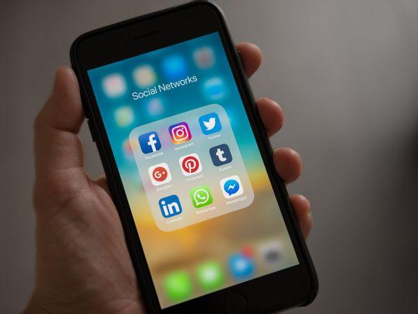 hält-handy-mit-screen-social-networks-in-der-Hand
