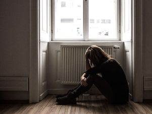 Junge Frau sitzt wegen dem ganzen Stress in der Arbeit am Boden.