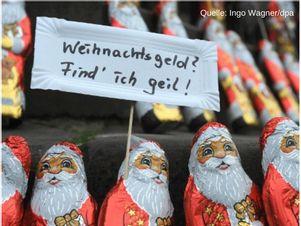 Schokolade Weihnachtsmänner halten Schild mit Aufschrift: Weihnachtsgeld? Find ich geil! (Quelle: Ingo Wagner/dpa)