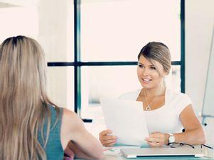 Junge Frau sitzt im Bewerbungsgespräch und redet über ihren Lebenslauf.