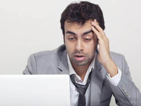 Mann sitzt vor PC und ist mit Job unzufrieden
