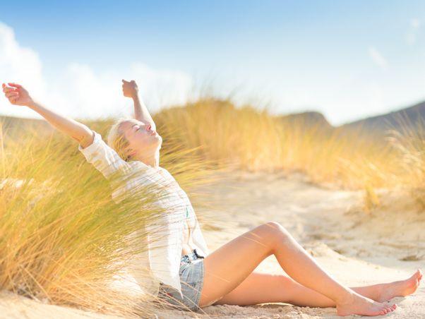 Frau sitzt morgens am Strand und streckt sich.