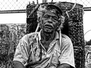 Alter Mann mit Korb sitz müde auf der Straße.