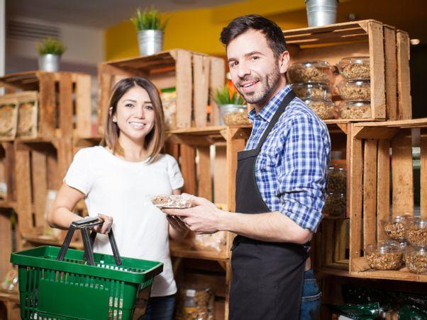 Junger Mann zeigt einer Kundin die Produkte des Einzelhandels.